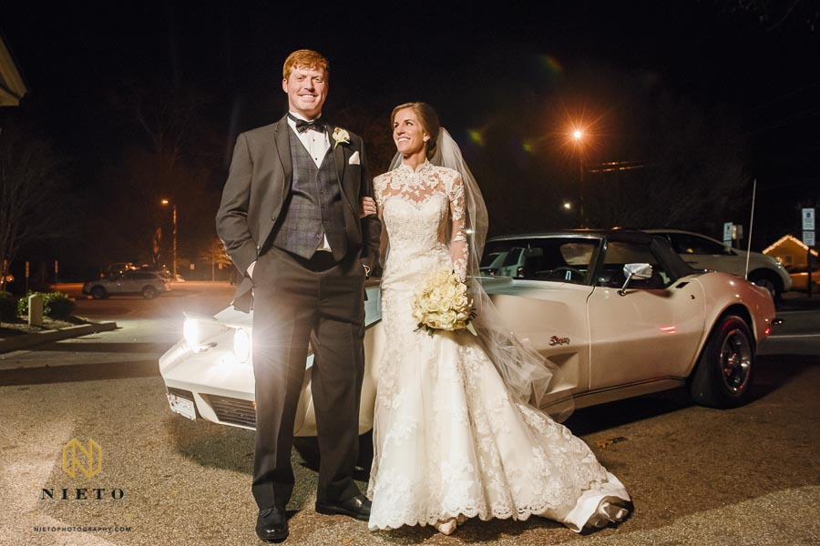 bride and groom posing in front of their vintage chevy stingray get-a-way vehicle