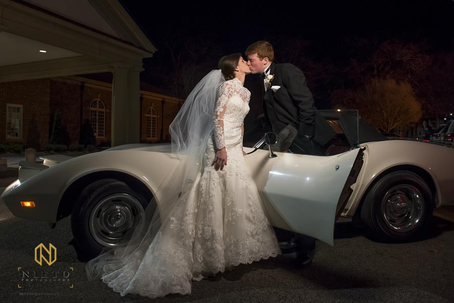 bride and groom kissing in front of their vintage stingray