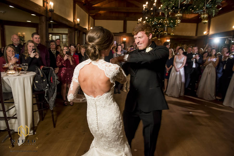groom intensely dancing with bride during their first dance at MacGregor Downs Country Club
