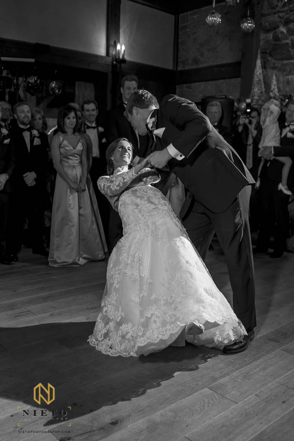 black and white image of groom dipping bride during their first dance