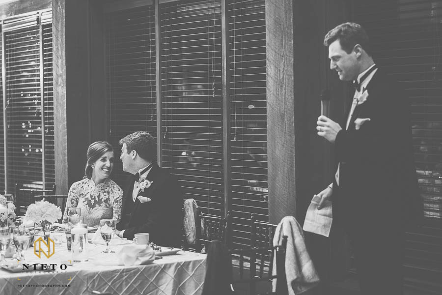 Black and white image of bride and groom smiling at each other as best man gives his toast