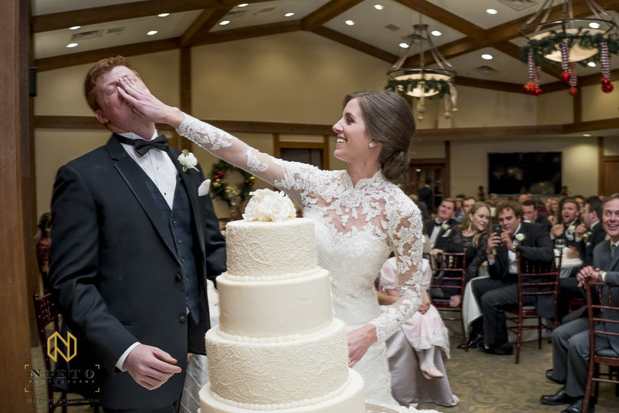 Bride smashing caking into the grooms face during their cake cutting at MacGregor Downs Country Club