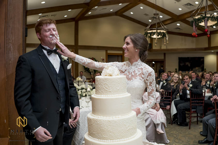 bride smears cake into the grooms face during the cake cutting at MacGregor Downs Country Club