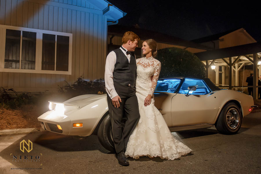 bride and groom posing against vintage stingray outside of MacGregor Downs Country Club