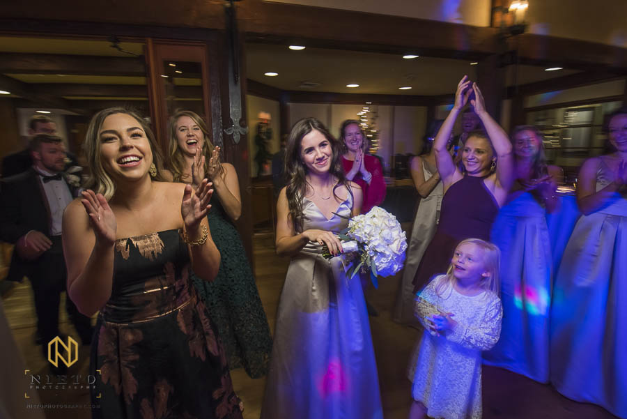 bridesmaid reluctantly smiles after she has caught the bouquet at MacGregor Downs Country Club