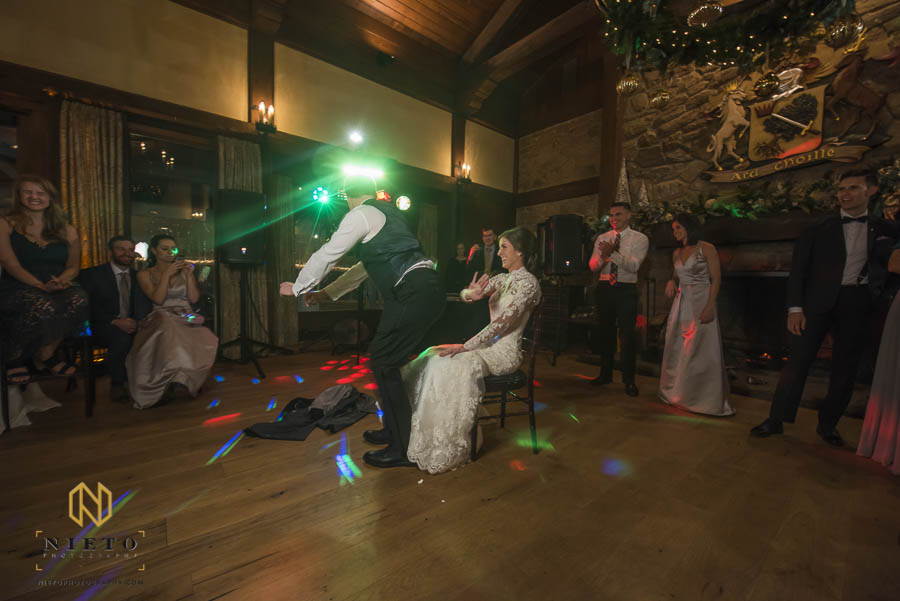 groom dancing around bride as she swats at him before he tries to remove the garter