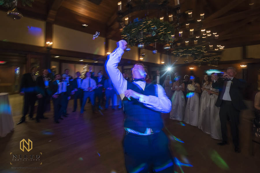groom tosses the garter over his shoulder to the waiting single men