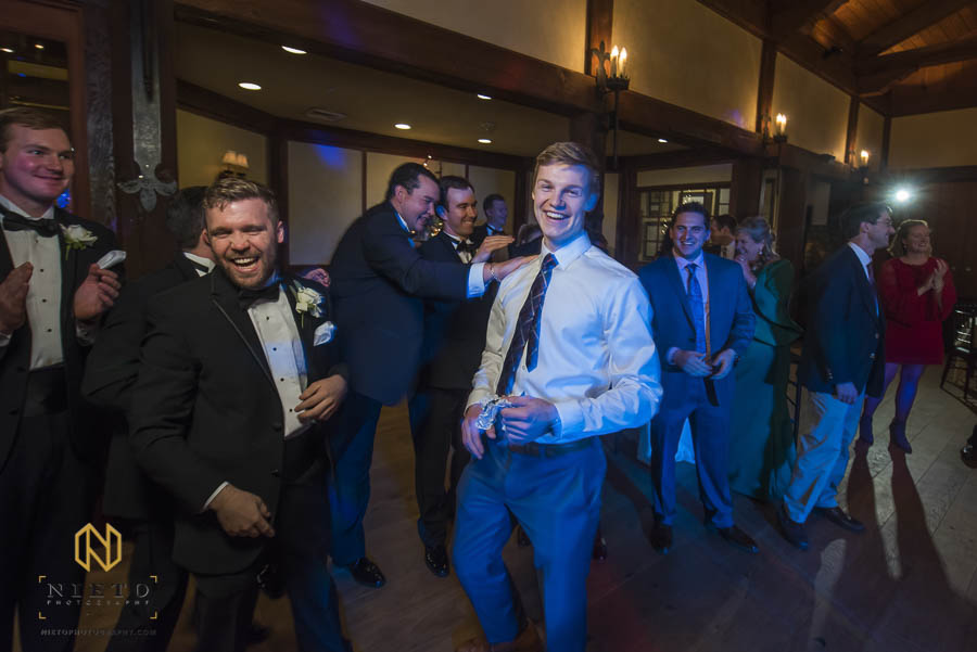single man who caught the garter smiles and laughs as the other men joke around