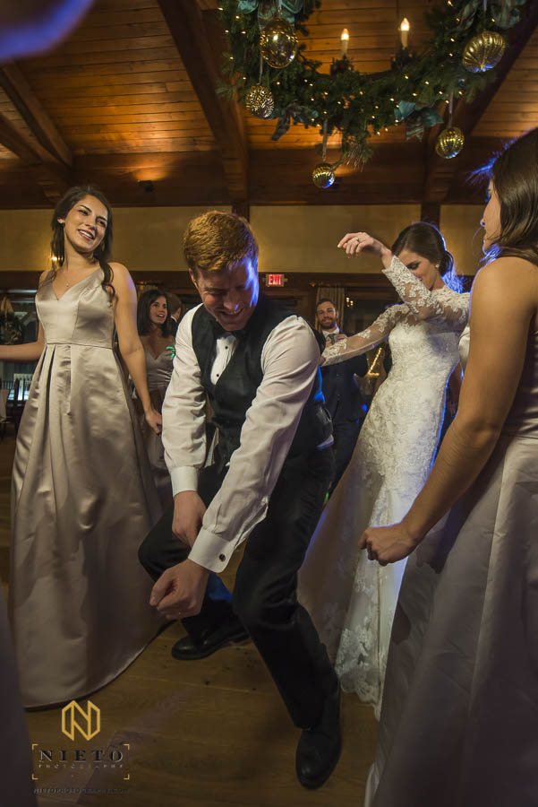 groom dancing with the bride and bridesmaids during the wedding reception at MacGregor Downs Country Club