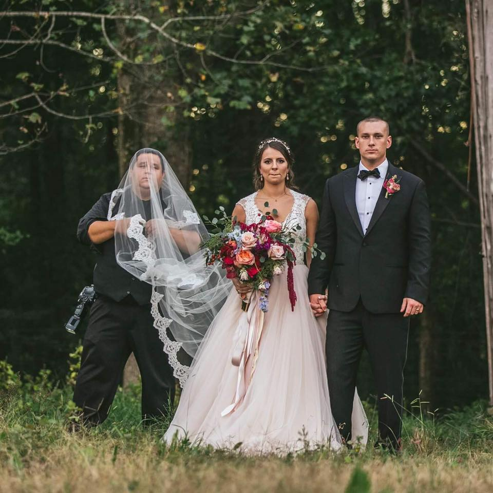 Chris Nieto with the brides veil over his face as the bride and groom stand in front of him at Cedar Grove Acres