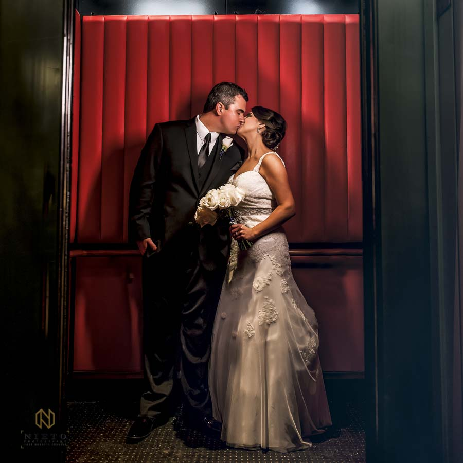 bride and groom kissing in the red elevator at 21c Museum Hotel in Durham NC