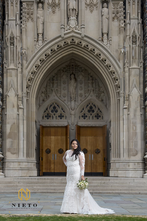 bride posing for her Duke Chapel bridal pictures in front of the main doors
