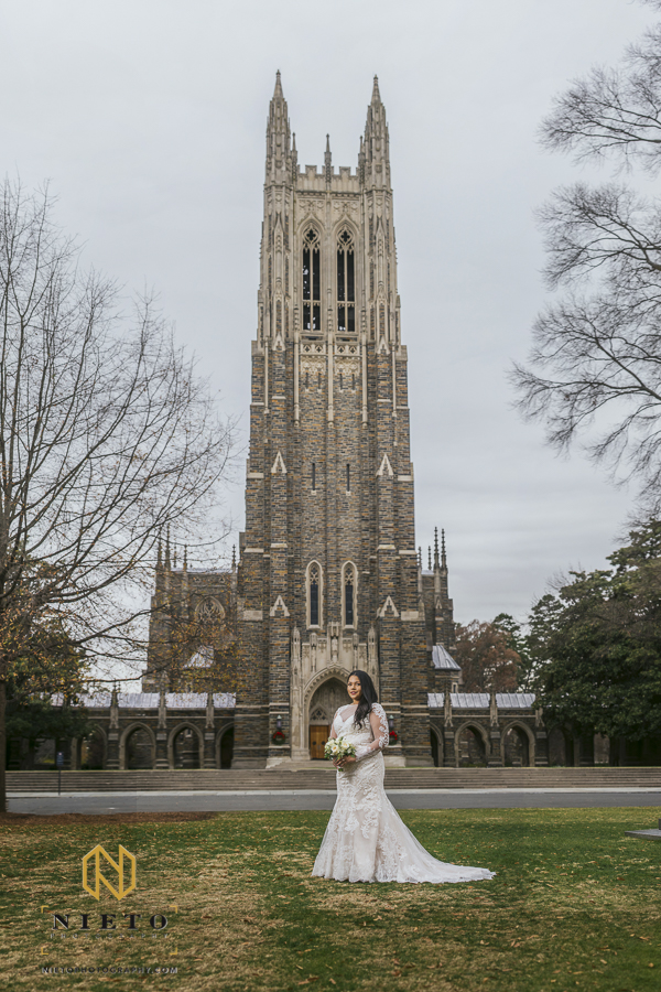 bride standing on the green lawn in front of Duke Chapel with the bell tower behind her