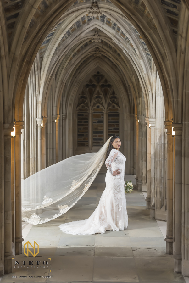 bride standing in an outdoor side hall of duke chapel as her veil blows in the wind