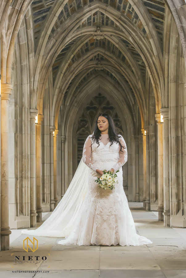 bride holding her wedding bouquet and looking at the ground posing for her Duke Chapel bridal portrait