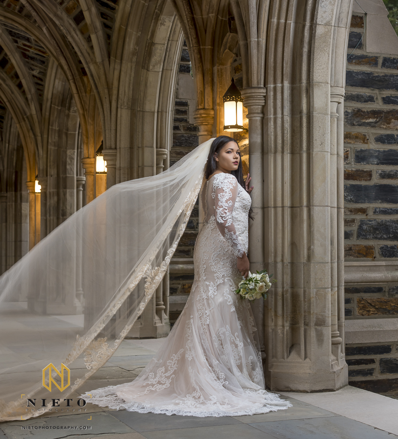 bride leaning against a stone column looking over her shoulder as her veil is picked up by the wind at Duke Chapel