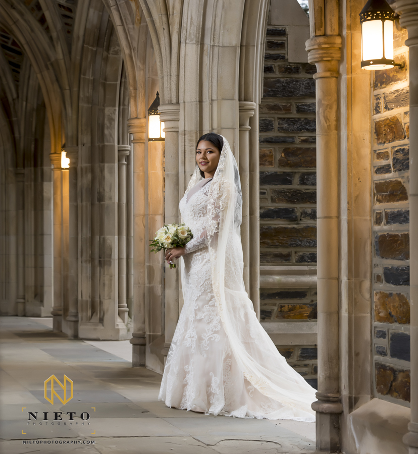 bride posing with her bouquet in the breeze way for her Duke Chapel portraits