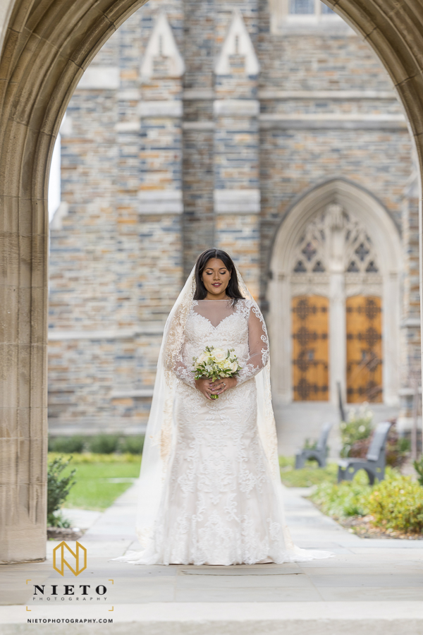 Duke Chapel bridal portrait of a bride in an elegant dress looking down at her bouquet