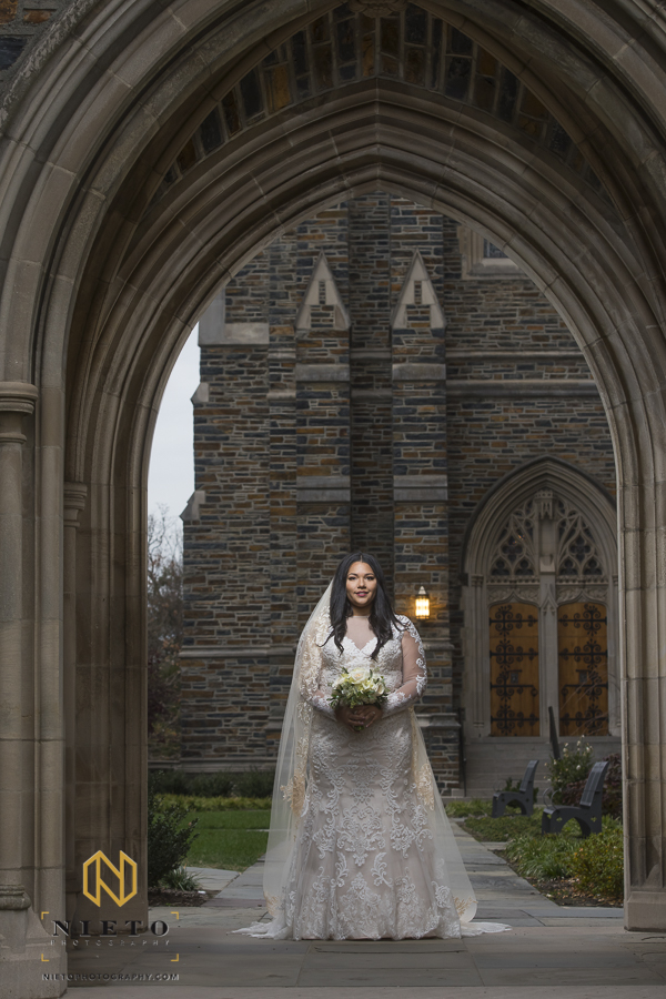 bring standing in a Duke Chapel arch way posing for her bridal pictures