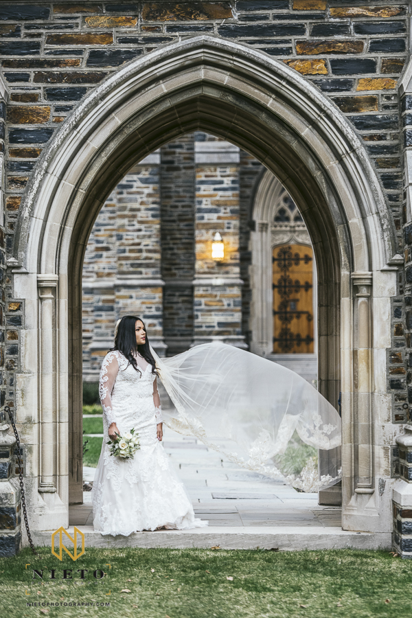 bride standing in one of the arch ways of at Duke Chapel with her veil blowing in the wind