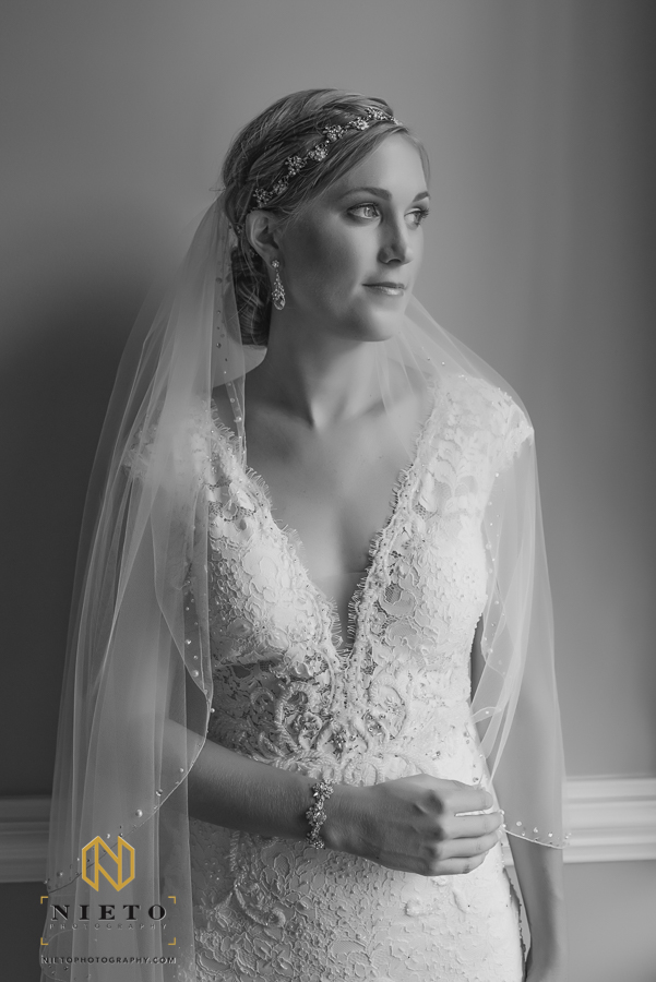 black and white portrait of bride standing against a wall holding her veil with one hand