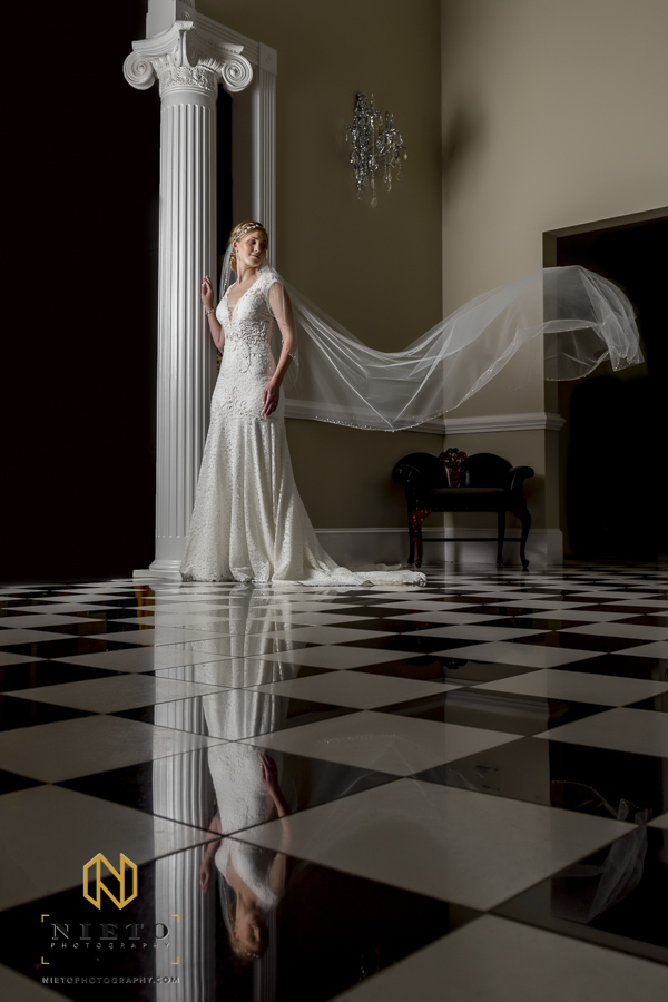 bride standing on the tile floor at the garden on millbrook with her veil in the air and reflection in the floor