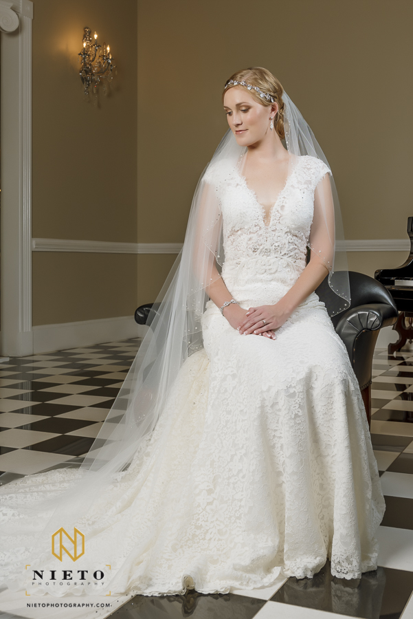 bride sitting in her wedding gown looking at the floor posing for her raleigh bridal portrait