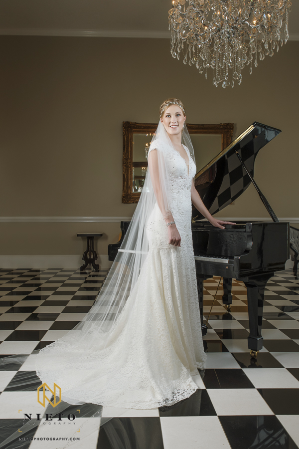 bride in her wedding gown standing by the piano at the Garden on Millbrook