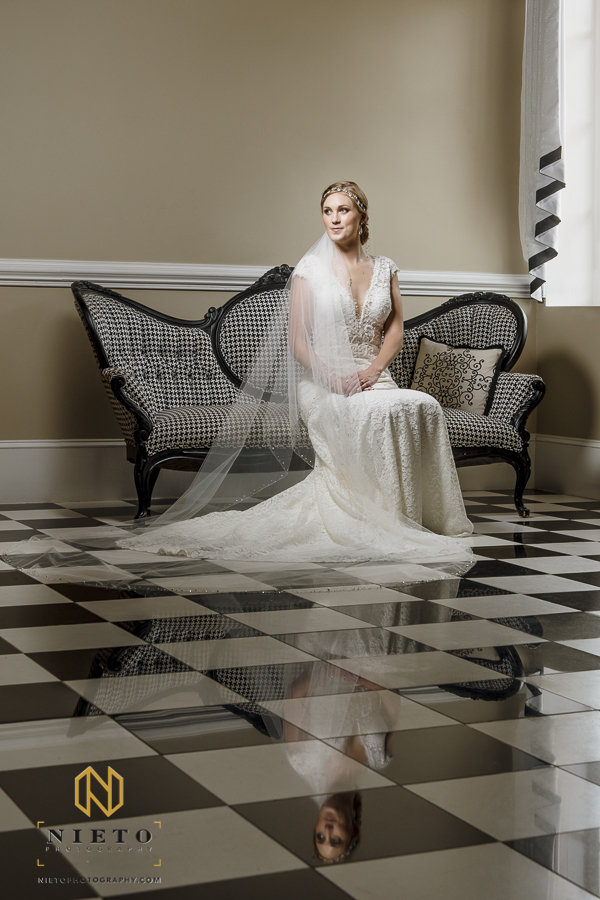 bride sitting on a black and white couch in her wedding gown and veil with her reflection on the floor.