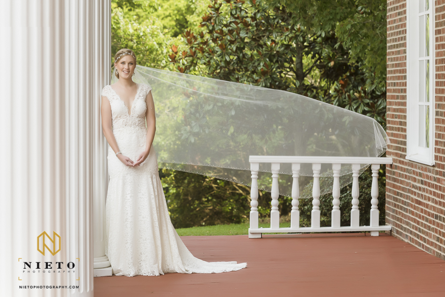 bride standing outside on the porch at the garden on millbrook with her veil blowing in the wind