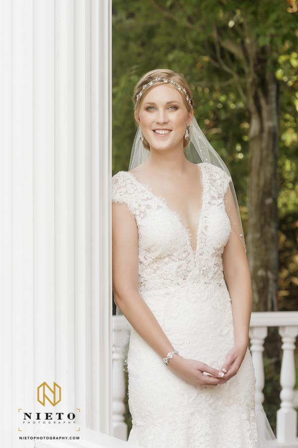bride leaning on a column in her wedding gown as she smiles for the camera