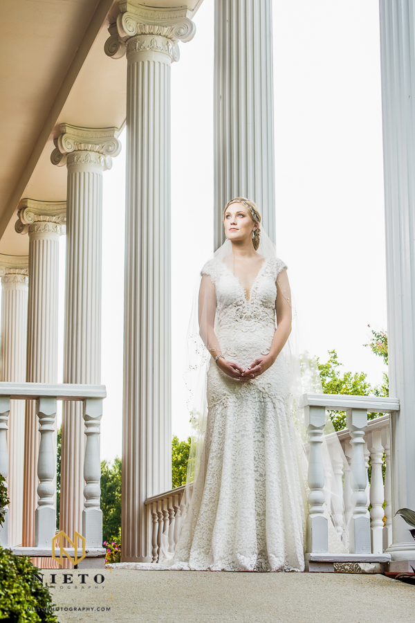 bride standing on the porch of the garden on millbrook posing for her Raleigh bridal portrait