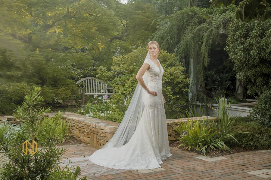 bride standing in the white garden at JC Raulston arboretum with her hand on her hip