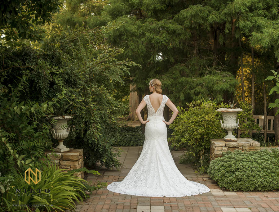 bride standing in the White Garden showing off the back of her dress