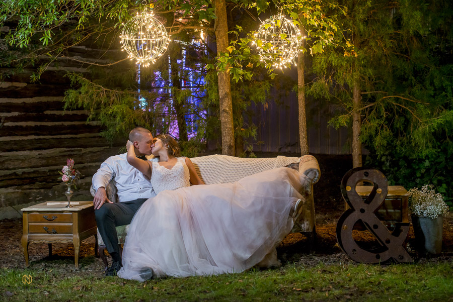 Couple kissing a couch outdoors under light orbs hanging in a tree at Cedar Grove Acres