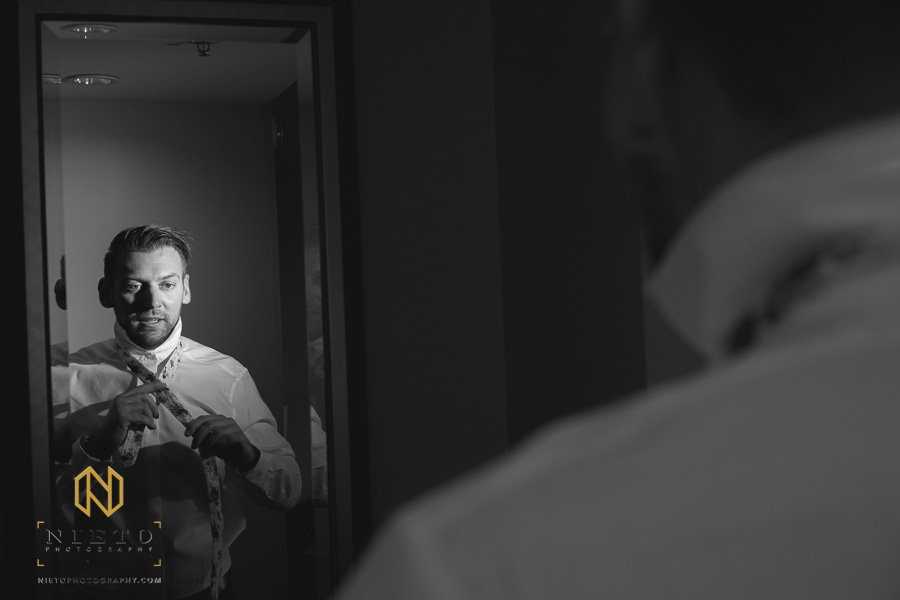 black and white image of groom tying his tie in a mirror
