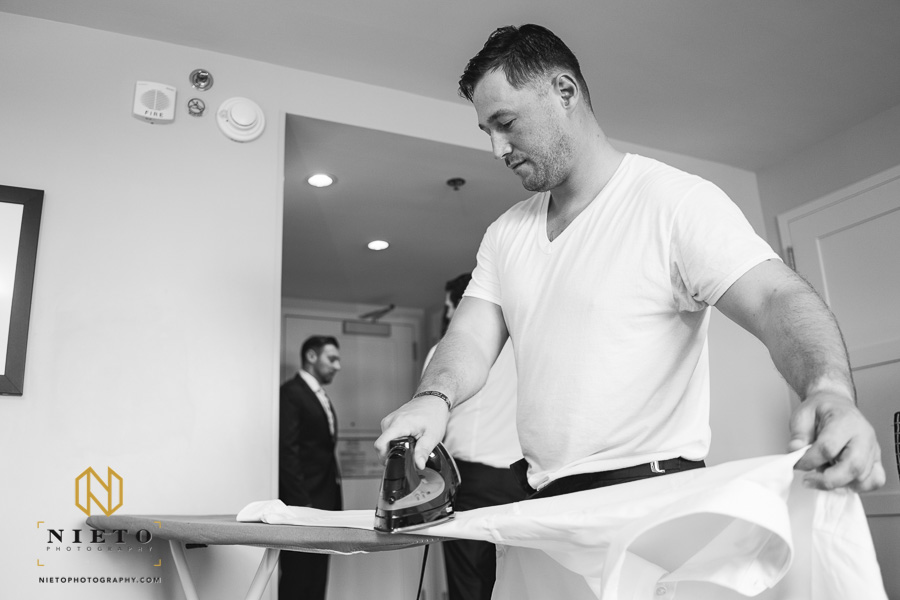 black and white image of the best man ironing his shirt in the grooms hotel room