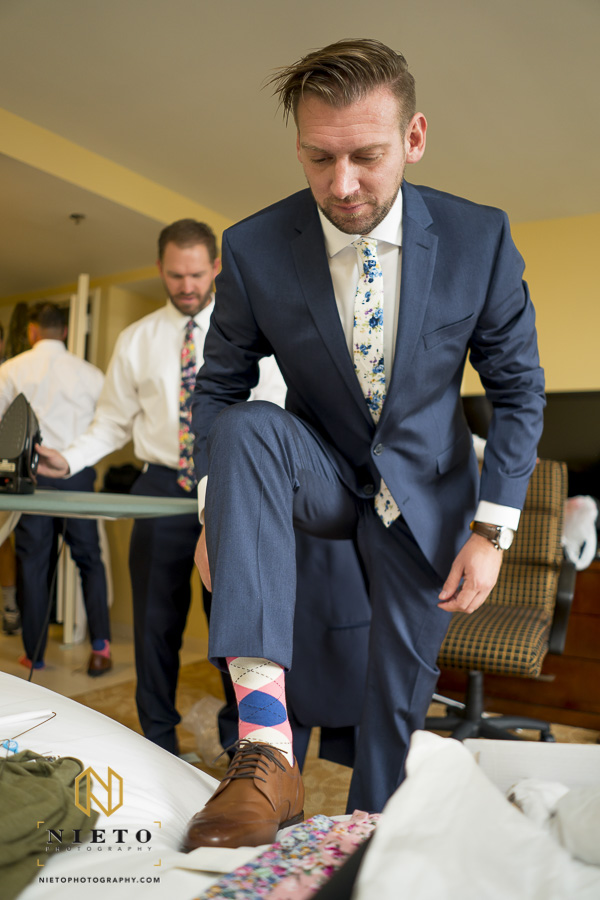 groom in his suit finishing tying his shoe in his hotel room