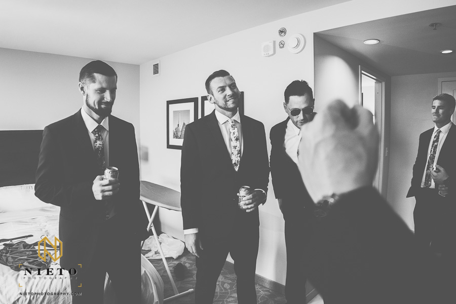 black and white picture of the groom and groomsmen standing around the hotel room drinking beer