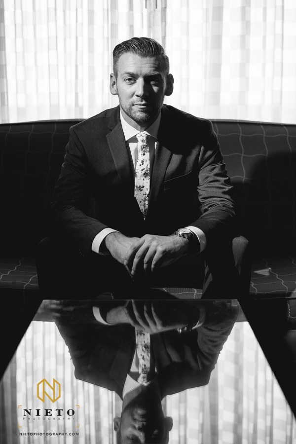 black and white image of the groom sitting with his reflection in the table in front of him