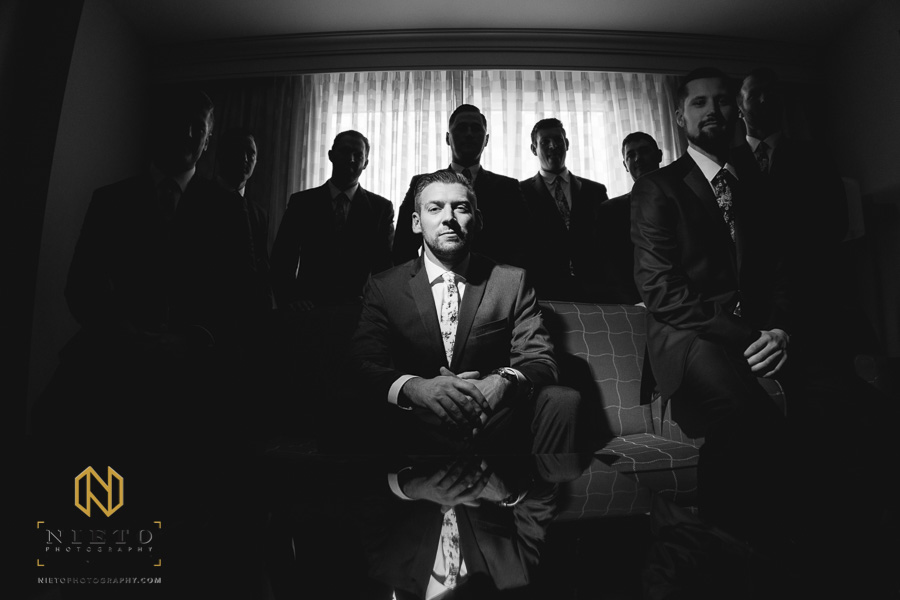 black and white image of the groom sitting with a light on his face as his groomsmen are in the shadows
