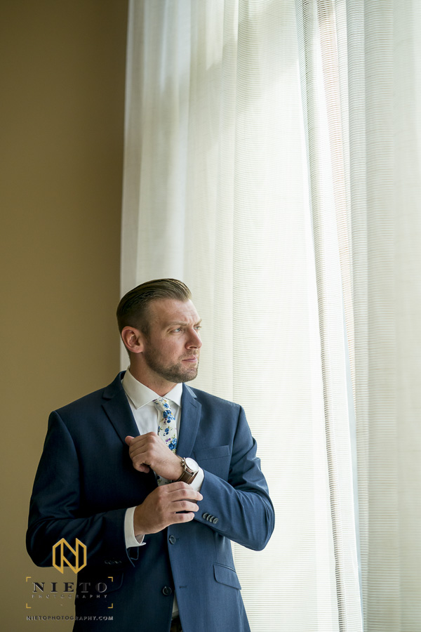 groom standing in front of a large window adjusting his shirt sleeve