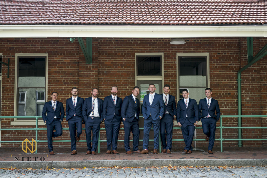groom and groomsmen posing against the green railing at Market Hall in downtown Raleigh