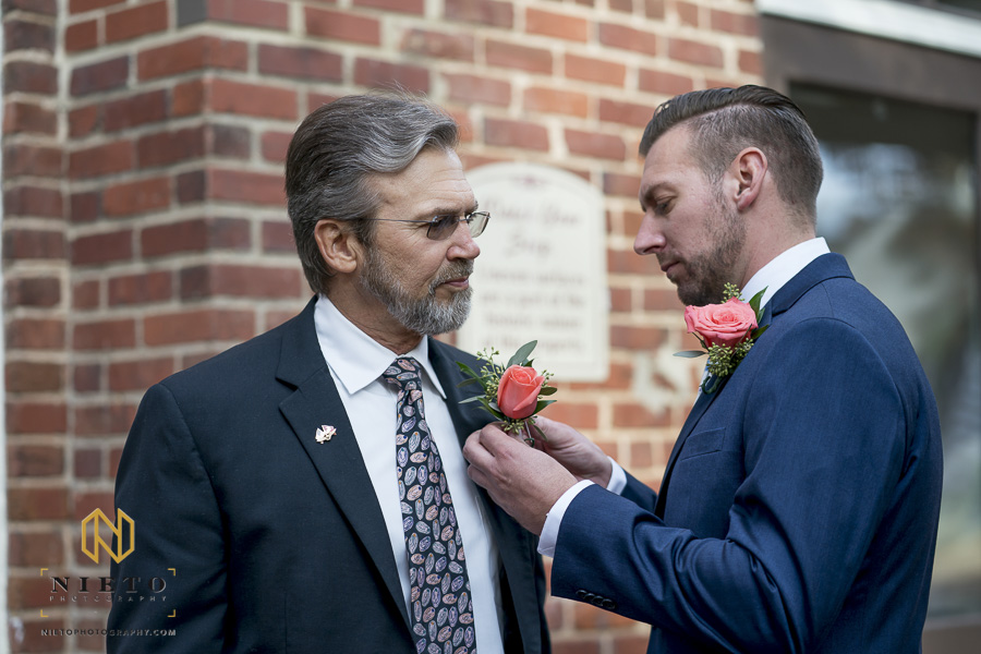 groom placing his fathers boutonniere on out side of Market Hall in Raleigh