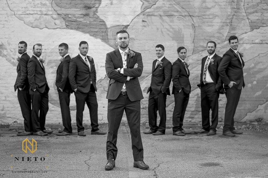 black and white image of groom posing with his arms crossed as his groomsmen pose behind him out of focus