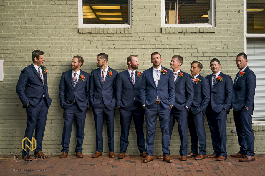 groom and groomsmen posing against green brick wall