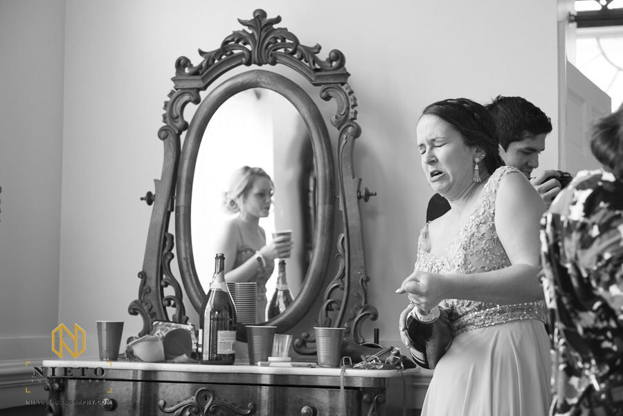 black and white image of a bridesmaid with her eyes closed as she struggles with the cork on a champagne bottle