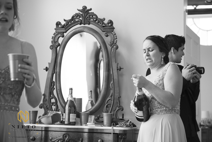 black and white image of a bridesmaid snuggling with a champagne bottle