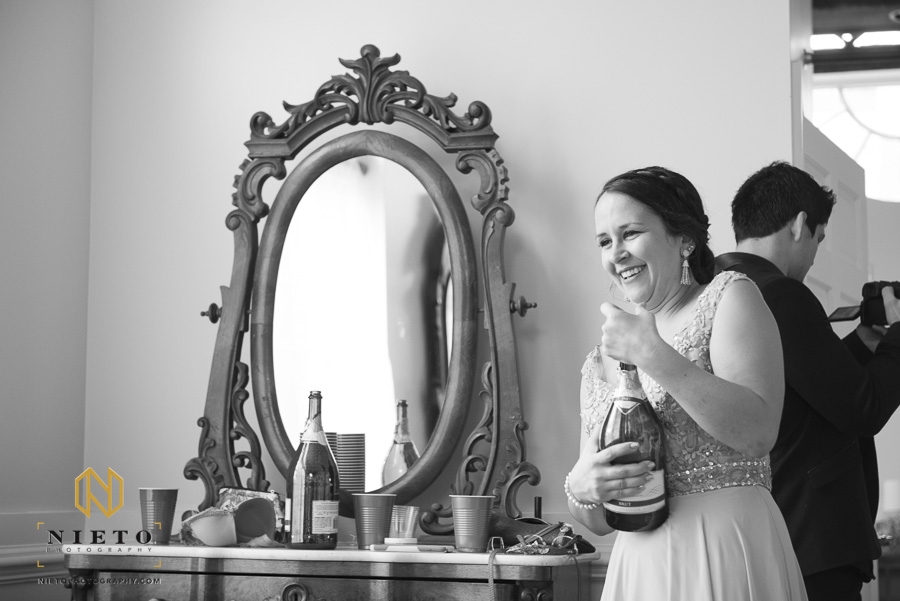 black and white image of a bridesmaid smiling and struggling with cork on a champagne bottle