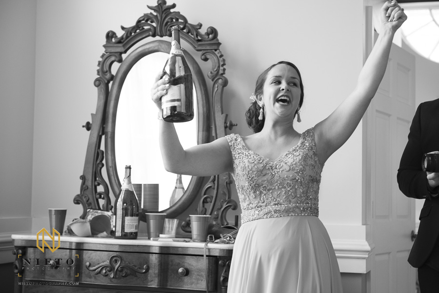 black and white image of a bridesmaid cheering as she takes off cork of champagne bottle